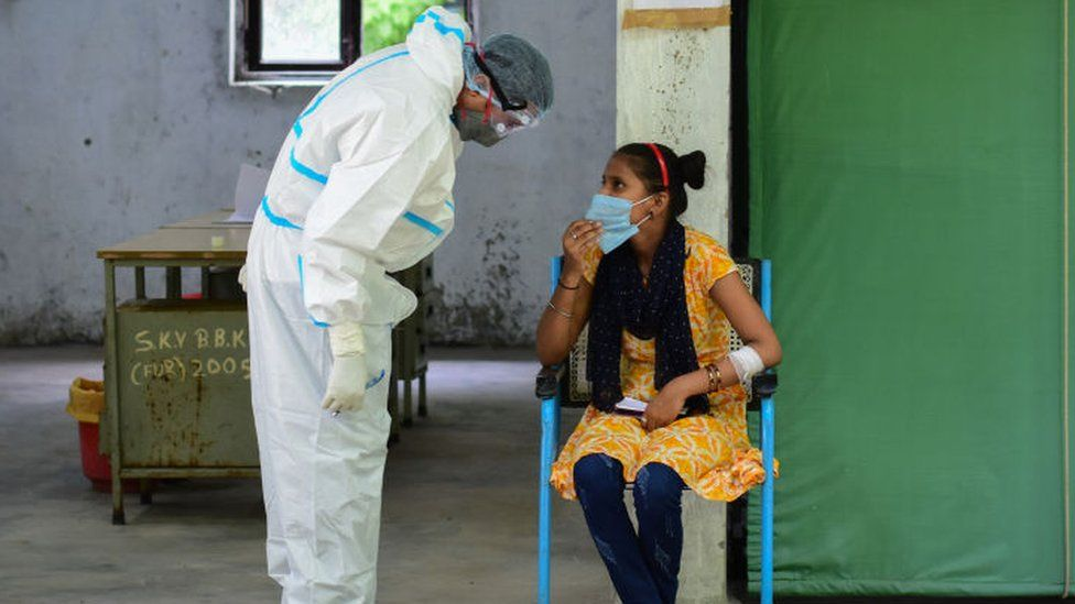 A health worker in PPE talking to a woman during a swab Covid-19 rapid antigen tests at a government school.