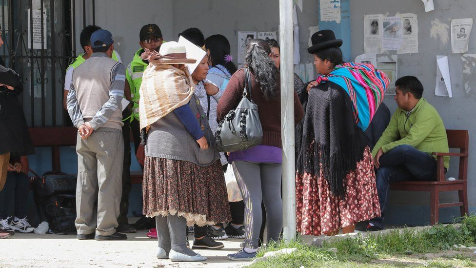 Relatives wait outside the morgue of the Clinicas Hospital, in La Paz, Bolivia