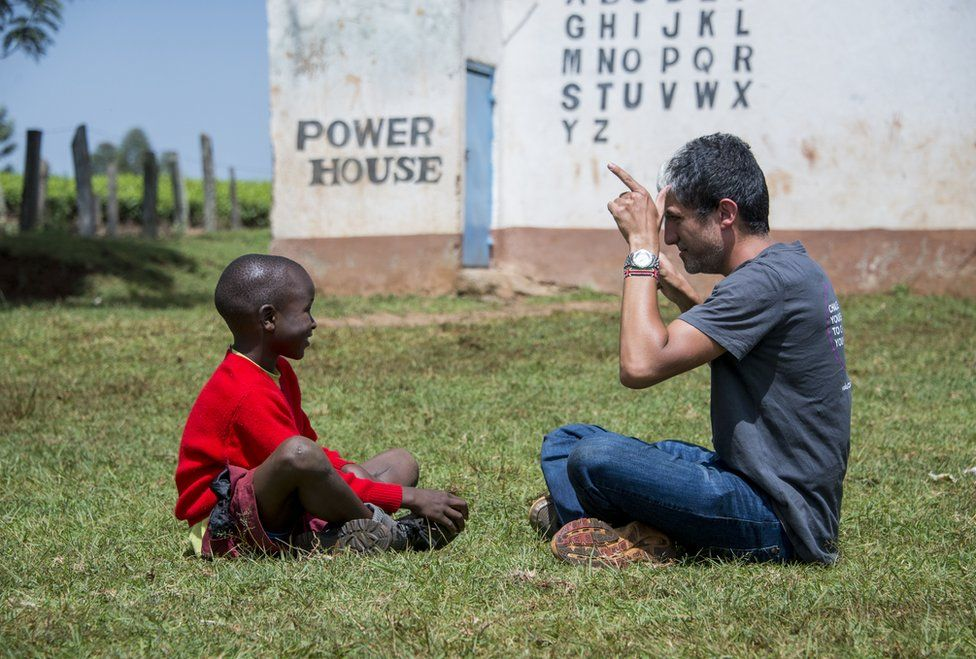 A man teaches a child sign language.
