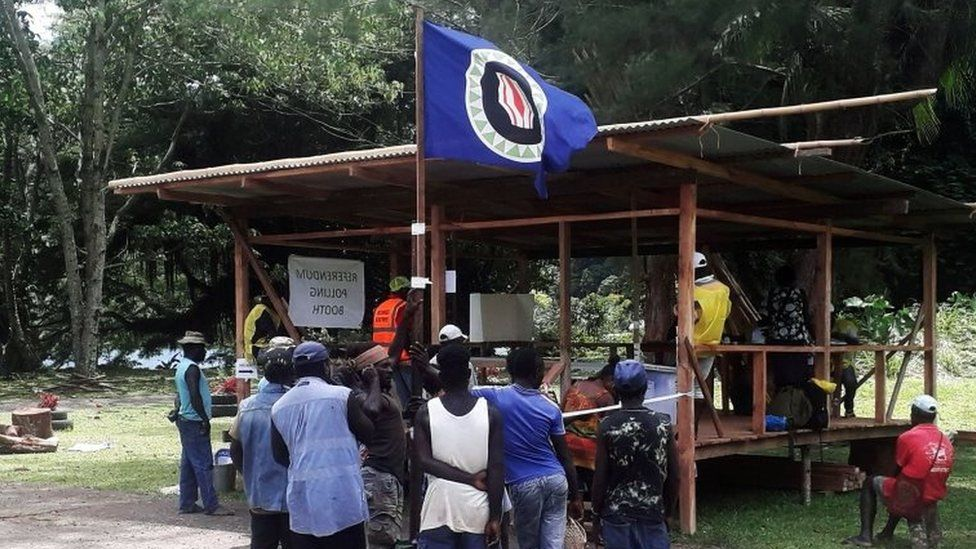 Voters hold a Bougainville flag at a polling station
