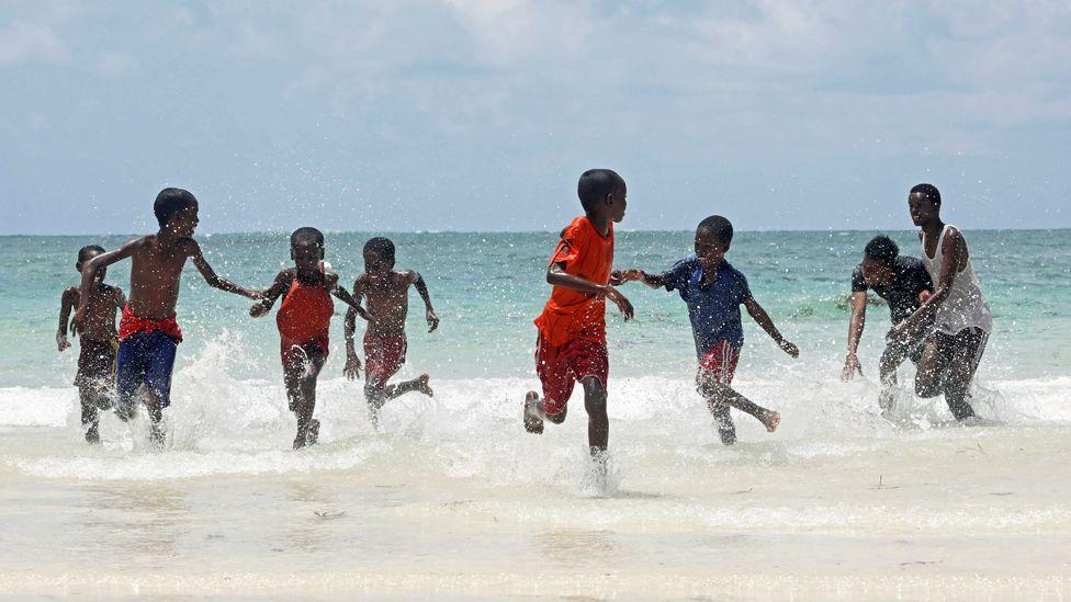 Children play on a beach in Mogadishu, Somalia - Friday 3 April 2020