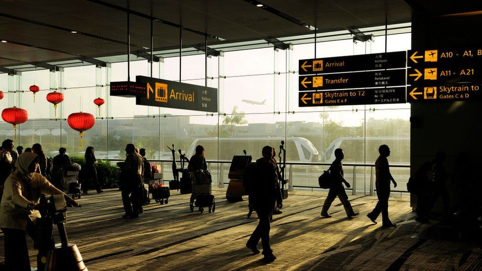 Passengers with bags and trolleys walking under signs for gates in Terminal 3 Heathrow