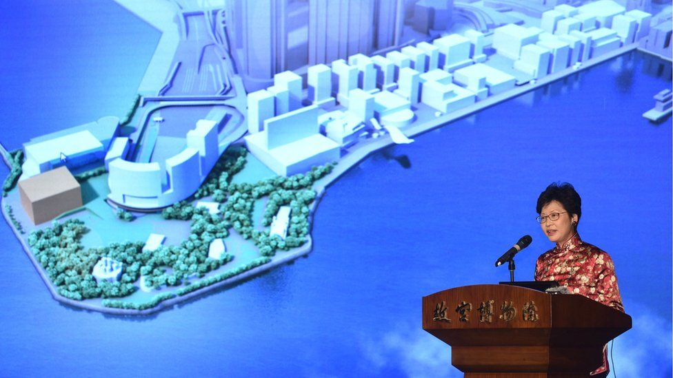 Carrie Lam introducing the museum at a podium, with a screen showing an image of the proposed building behind