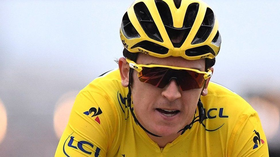 Geraint Thomas in action wearing a yellow crash helmet and sunglasses