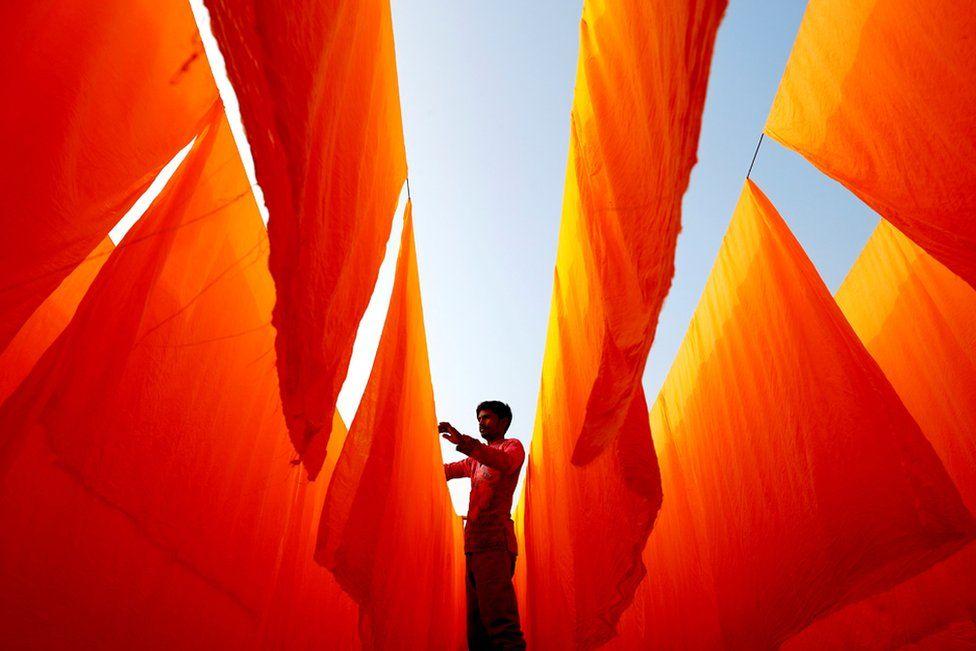 A worker dries fabrics after applying colour at a dye factory in Narayanganj, Bangladesh, 13 January 2021.