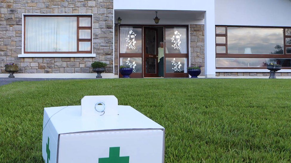 A package with a pharmacy logo on it is seen on the grass in a front garden