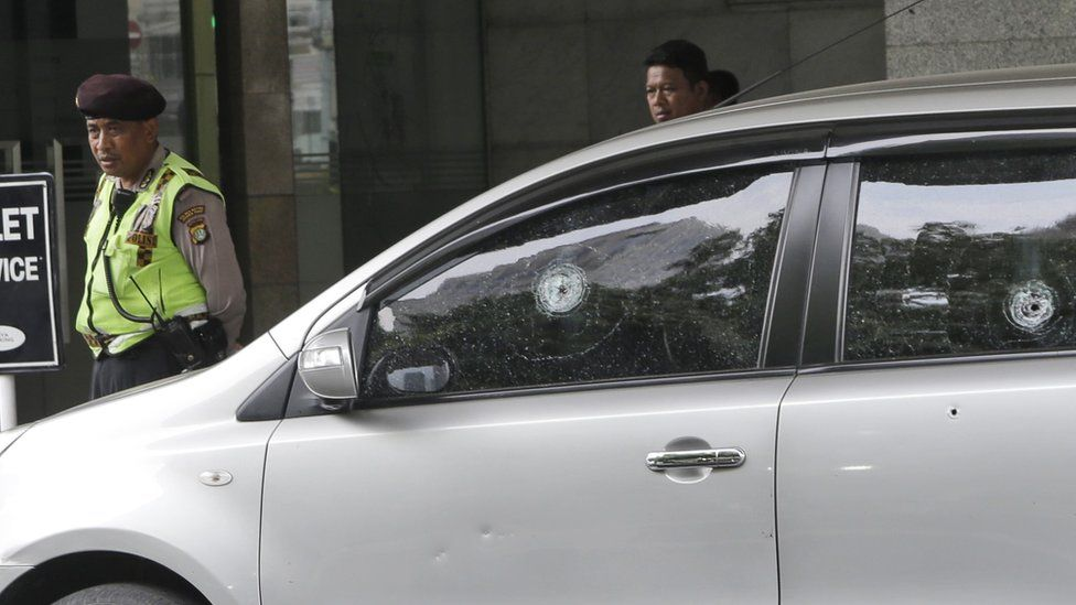 Bullet holes in the window of a car outside the Starbucks cafe targeted in Jakarta, 15 January