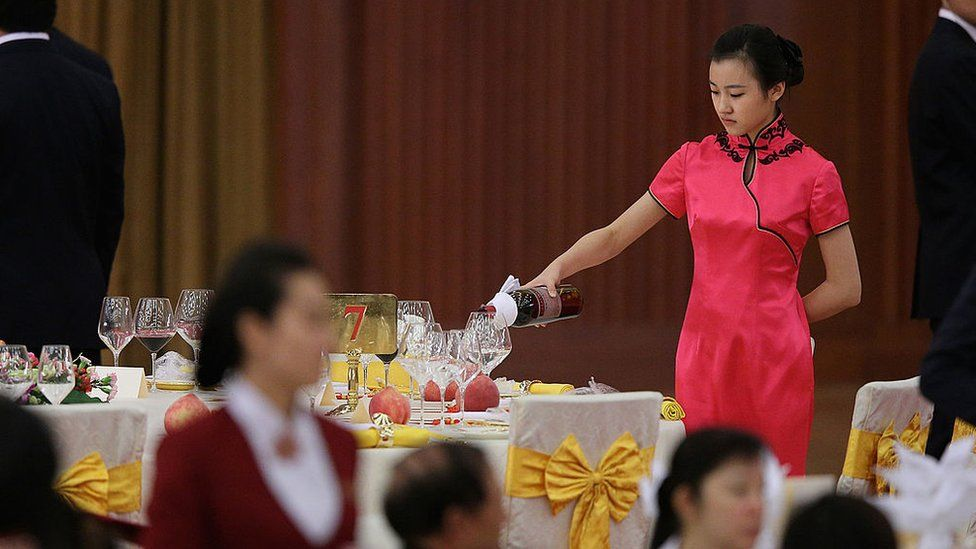 A hostess pours wine during a banquet in Beijing