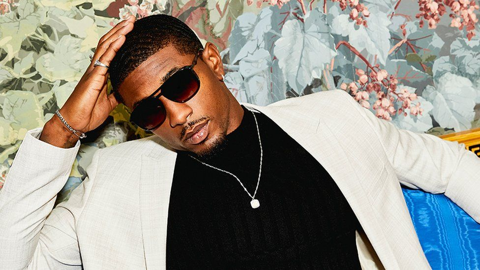 Love Island star Ovie Soko models his ASOS collection wearing dark sunglasses, a white suit and a dark polo neck sweater