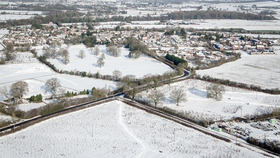 Vllage of Rowde and surrounding fields in Wiltshire remain covered in a blanket of snow.