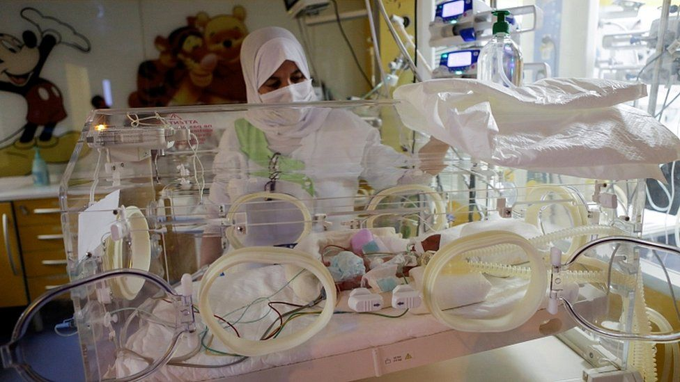 A nurse takes care of one of the newborn nonuplets, lying in an incubator, at the private clinic of Ain Borja in Casablanca, Morocco May 5, 2021