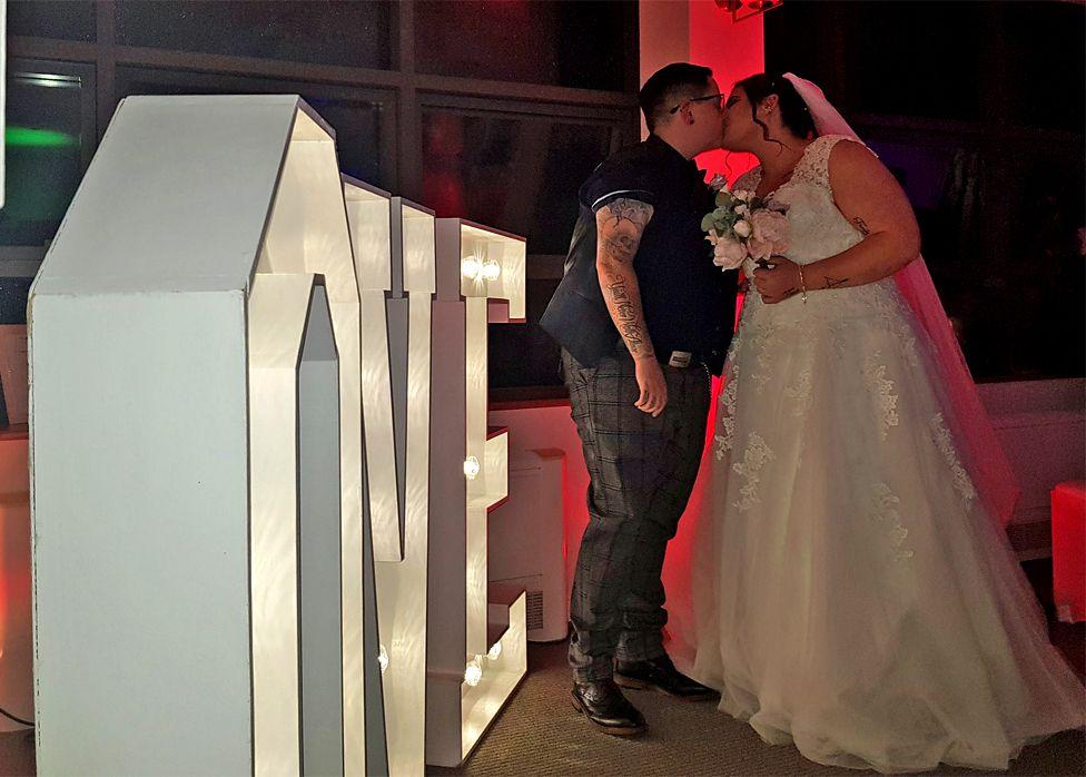 A wedding couple kiss