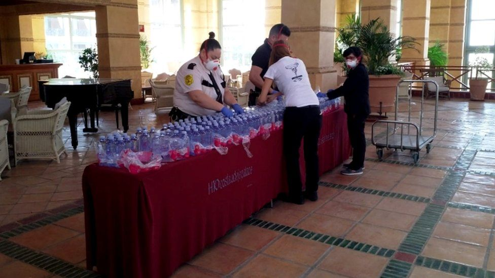 Masked hotel staff prepare water bottles for guests