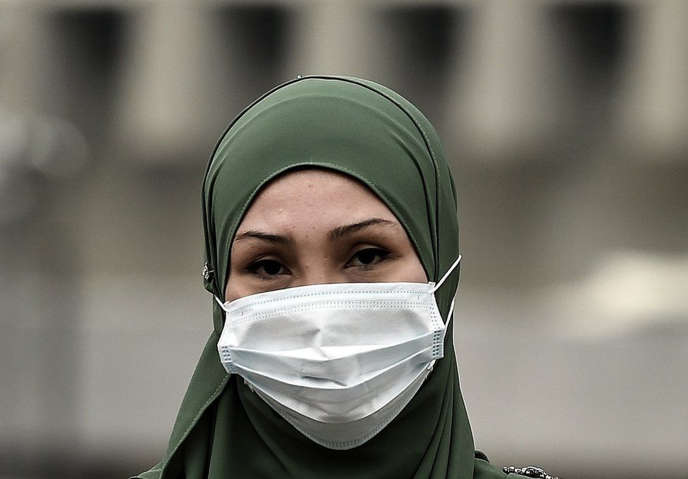 A Malaysian Muslim woman wearing a face-mask crosses a road during thick haze over Kuala Lumpur on 15 September 2015.