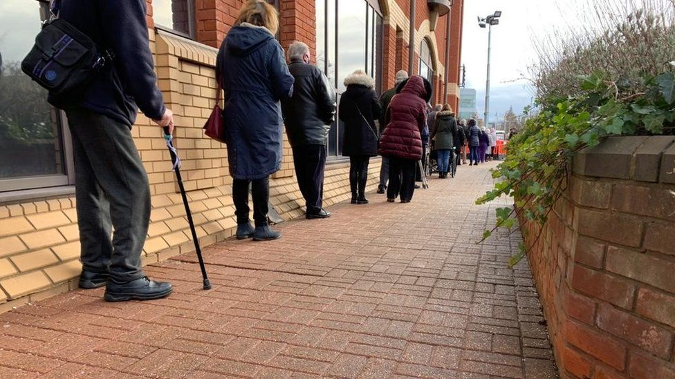 People queueing outside Robertson House in Stevenage for their vaccine