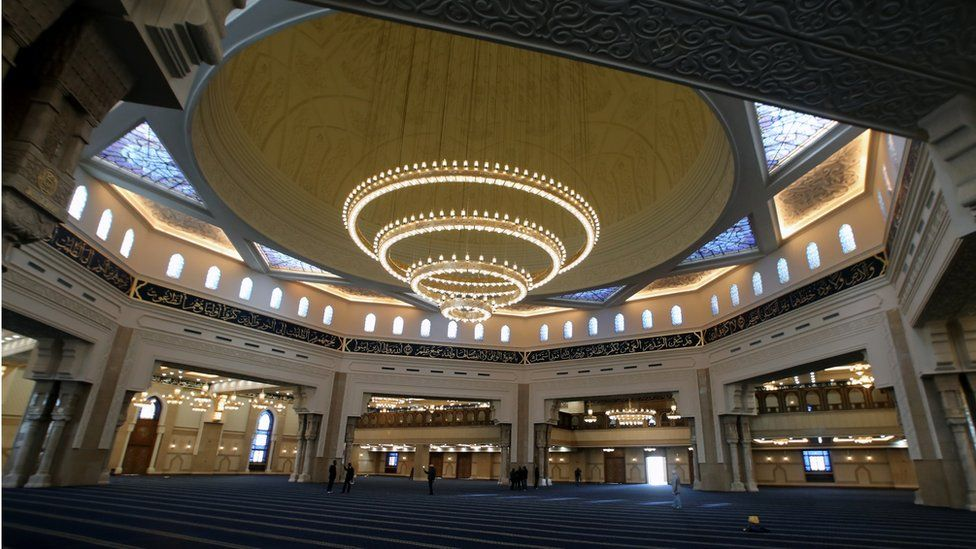 Laborers work inside the newly-constructed Al-Fattah Al-Alim mosque at the new administrative capital, 45km east of Cairo,