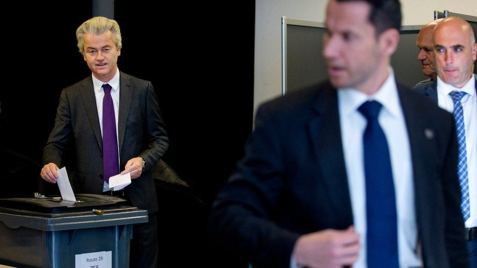 Bodyguards stand watch as firebrand Dutch lawmaker Geert Wilders, left, casts his vote in a non-binding referendum on the EU-Ukraine association agreement in The Hague, Netherlands, Wednesday, April 6, 2016.