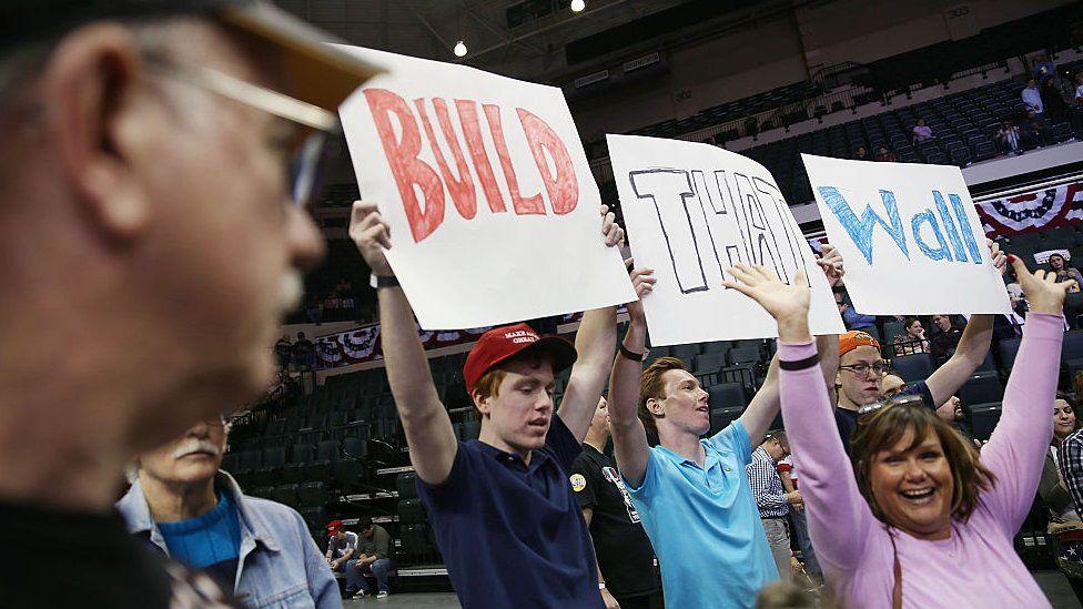 """Build the wall"" signs at a trump rally"