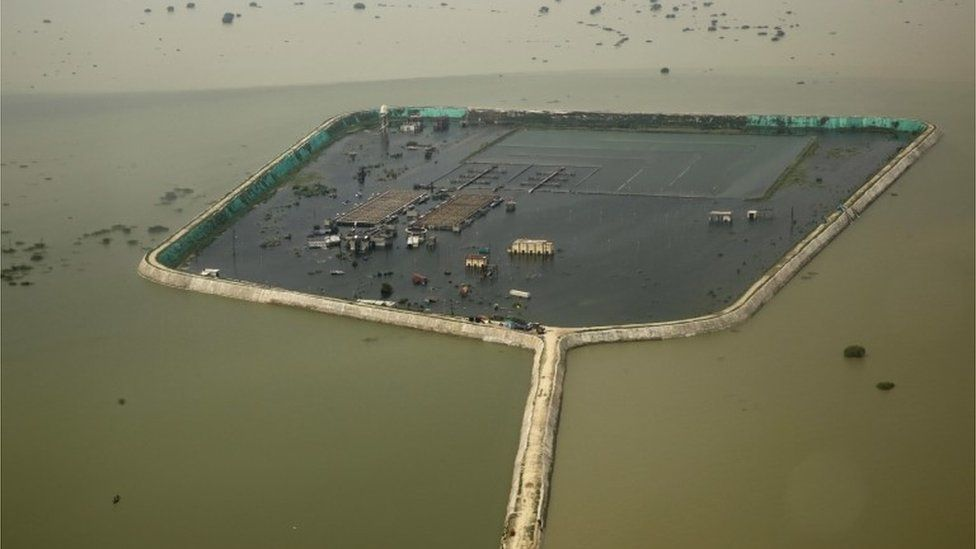 A factory and a residential area are seen marooned in the river Ganges flood waters on the outskirts of Allahabad, India, Friday, Aug. 26, 2016.
