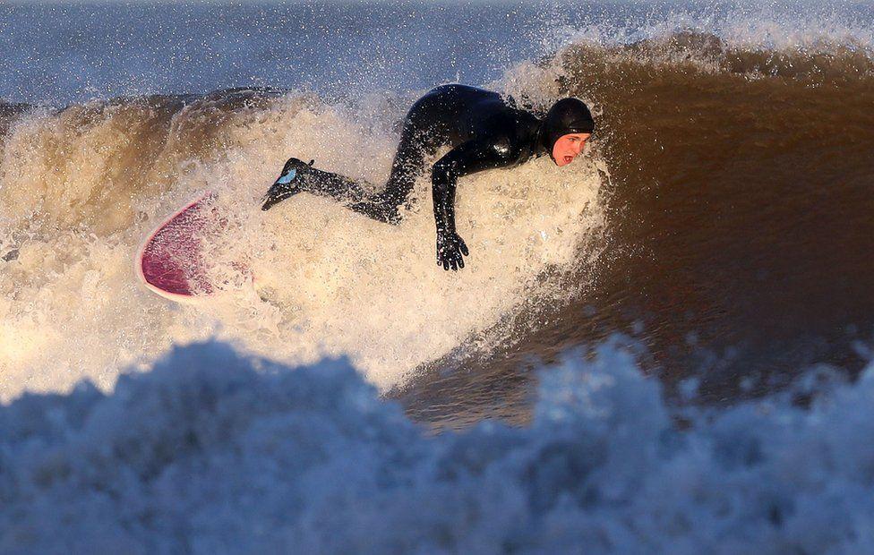 A surfer surfs a wave