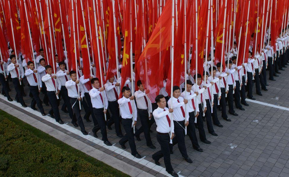 People holding flags during the military parade for the 70th anniversary of the founding Workers' Party, Pyongyang, North Korea - Saturday 10 October 2015