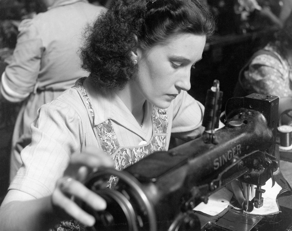 Woman using a vintage Singer sewing machine in the 1950s