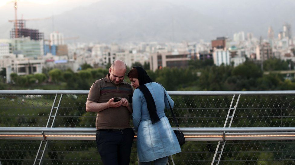 An Iranian couple look at pictures on their smartphone on the 'Nature' bridge in the capital Tehran on 2017