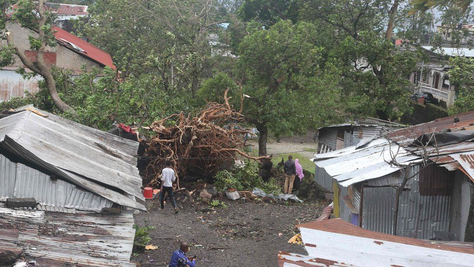 People stand by damaged houses and fallen trees in Comoros