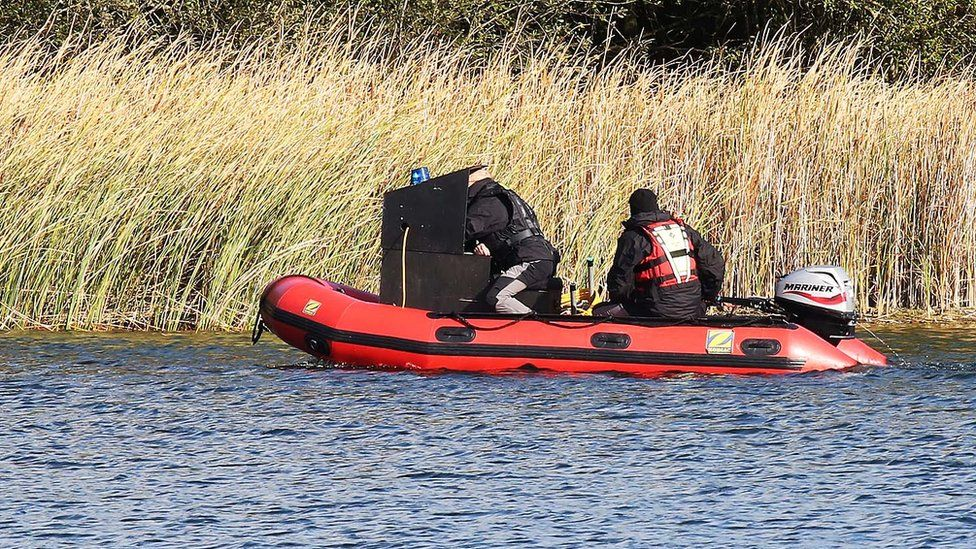 Officers search the lake