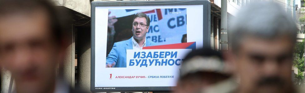 People walk past an election poster of poster of Prime Minister of Serbia and Serbian Progressive Party (SNS) leader Aleksandar Vucic in Belgrade