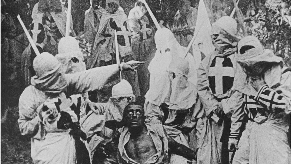 Black and white photograph of a group of Klansmen surrounding freedman Gus (played by white actor Walter Long in blackface) in a scene from Birth of Nation