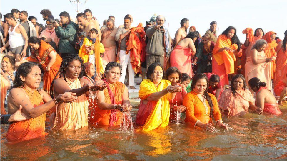 Women taking a dip at the Sangam