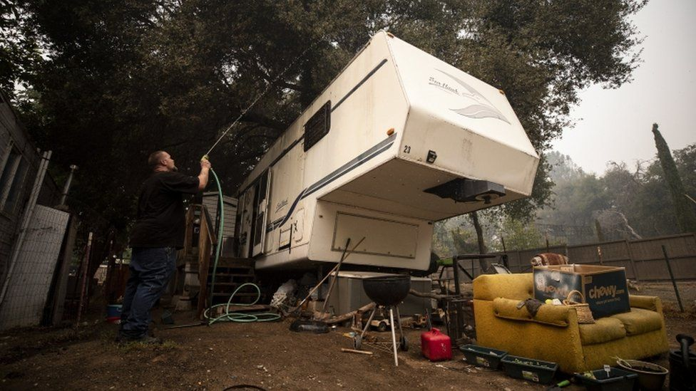A person hoses his trailer during preparations for evacuation from the Creek Fire, in the Sierra National Forest, 7 September 2020