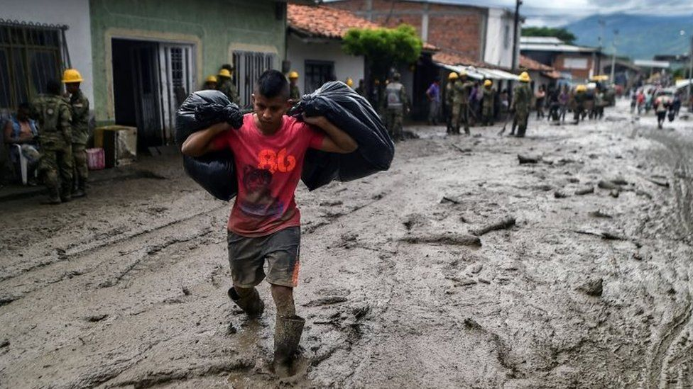 A young man carries his belongings across a muddy street, after a mudslide due to heavy rains affected Corinto in Cauca department, southwest Colombia on November 8, 2017