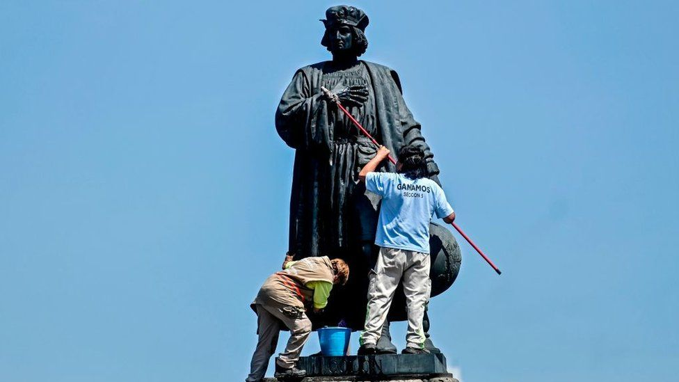 Municipal workers clean a statue of Christopher Columbus, which was protected by a metal fence after activists called to tear it down on social networks, in Mexico City, on October 12, 2020.