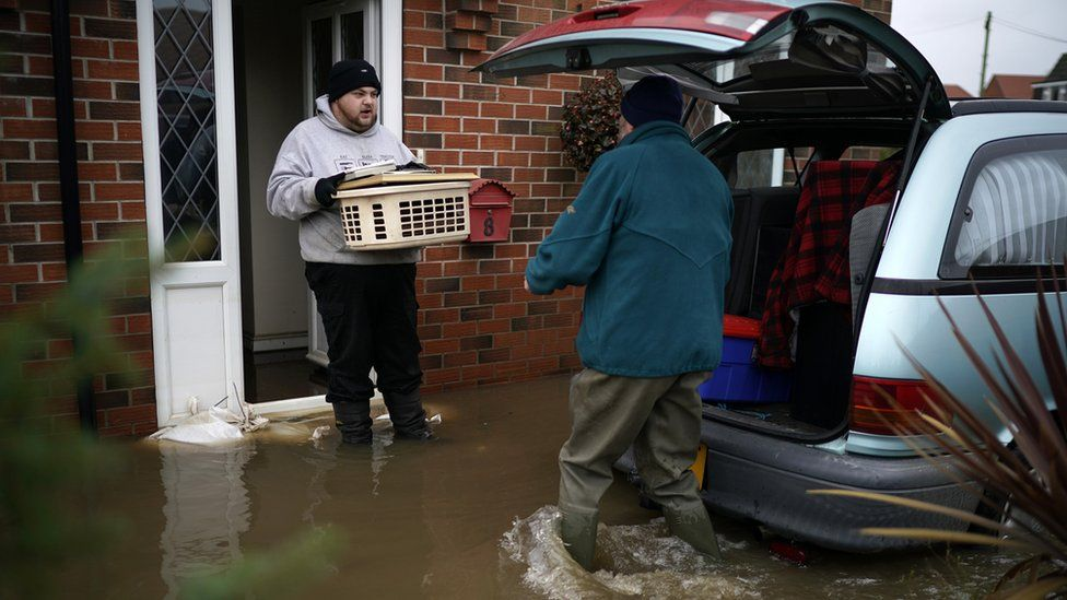 Two men carrying things out of a house hit by flooding and putting it in a car boot