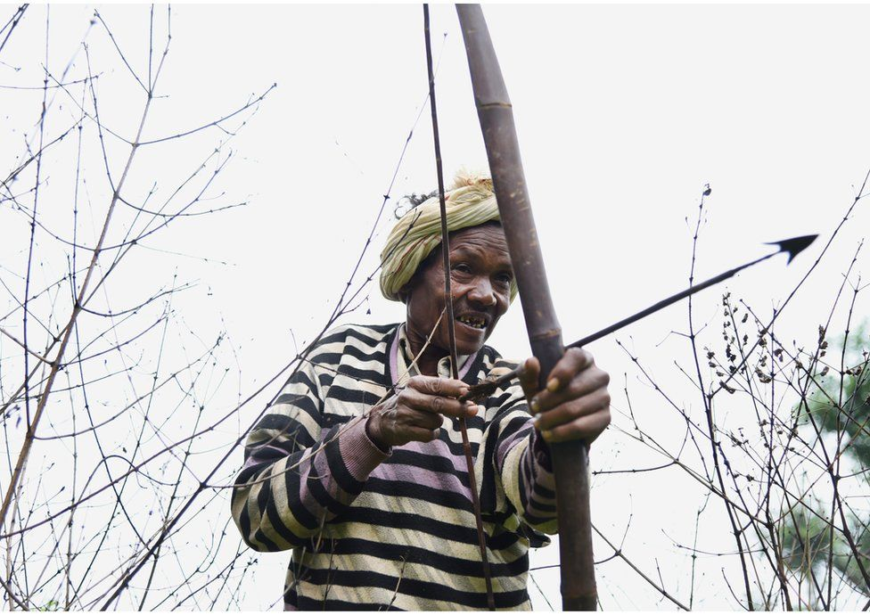 A man uses his bow and arrow to hunt wild animals.