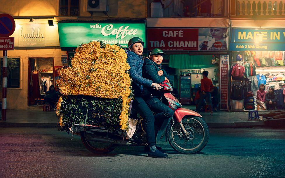 دو افراد موٹر سائیکل پر سوار ہیں جبکہ اس کے پچھلے حصہ پر پیلے پھول لدے ہیں