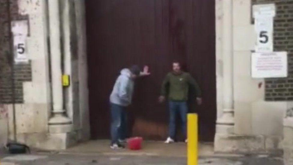 Two men at prison gate