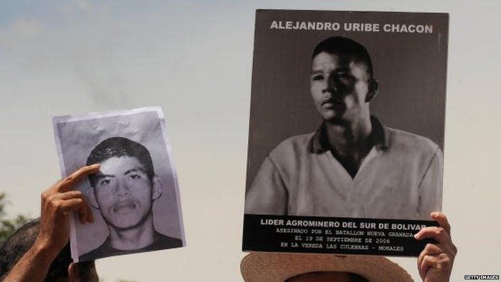 People hold pictures of murdered relatives during a march against the false positives on 6 March, 2009, in Bogota.