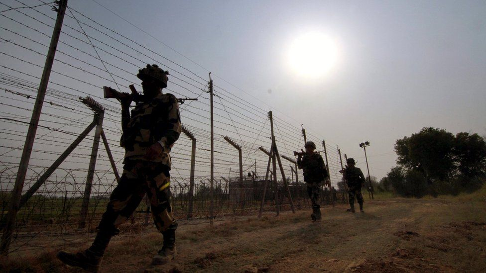 A file picture dated 10 May 2016 shows members of the Indian Border Security Force (BSF) patrolling near the fence at the India-Pakistan International Border at Budwar post of Arnia sector, about 40km from Jammu, the winter capital of Kashmir, India.