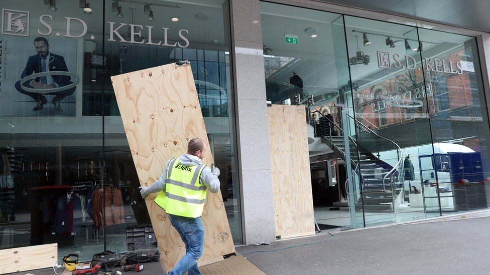Workmen putting up hoarding