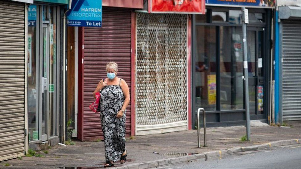 A woman walking along Cardiff street with closed shops behind