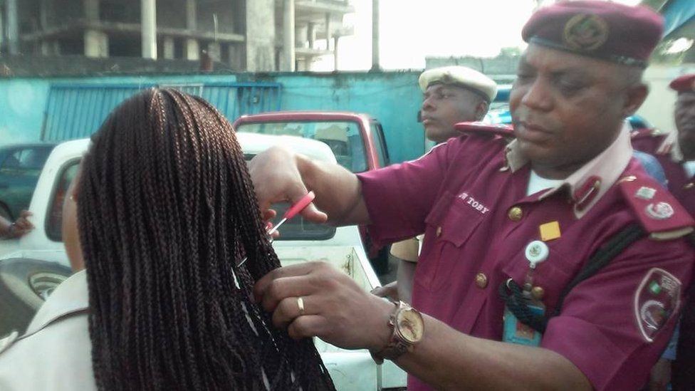 Man wearing a maroon beret and uniform takes scissors to a female employee's hair