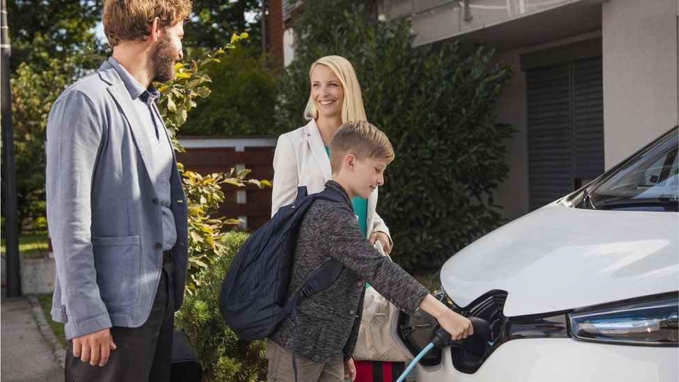 Family charging car in front of home