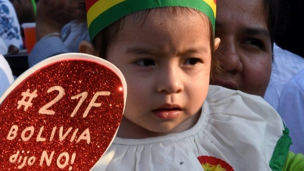 """A child holds a sign reading """"On 21F Bolivia said no!"""""""