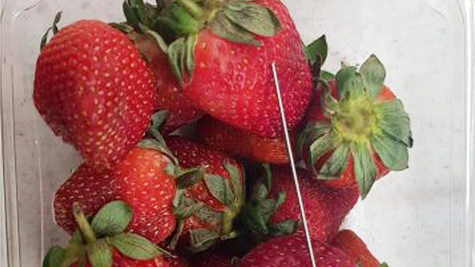 A needle next to strawberries