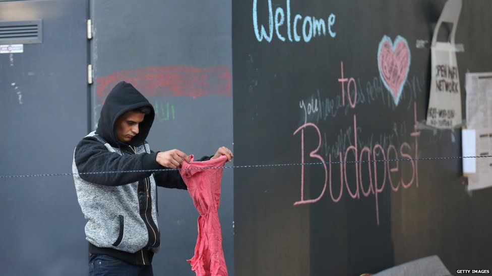 A migrant sorts through donated clothes at Keleti train station in Budapest in Budapest, Hungary, on 8 September 2015