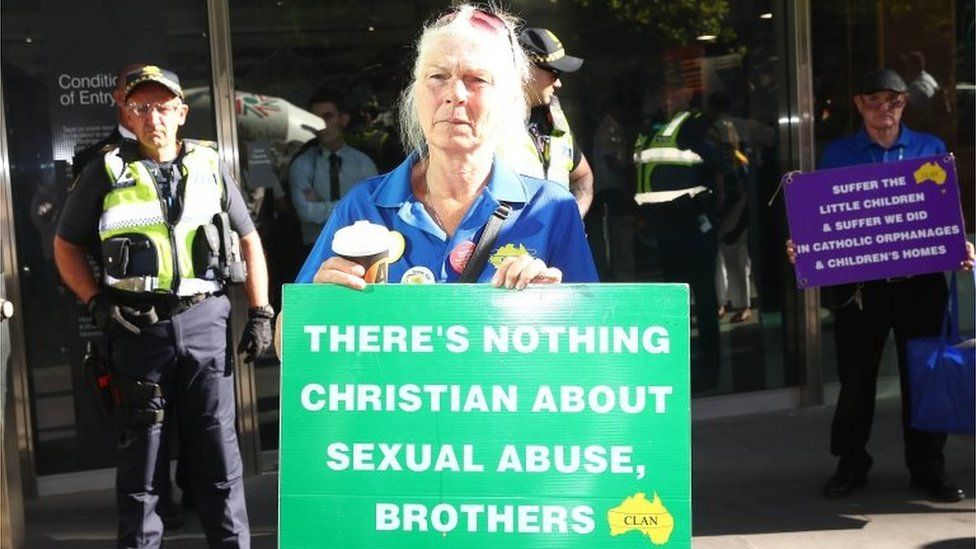 """A protester outside a court hearing for Pell holds a sign saying: """"There's nothing Christian about sexual abuse, brothers."""""""