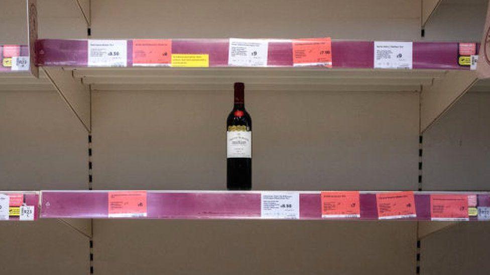 Bottle of wine on an empty supermarket shelf